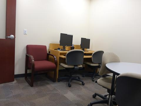 East Study Room equipped with a round table, chairs, and two desktop computers