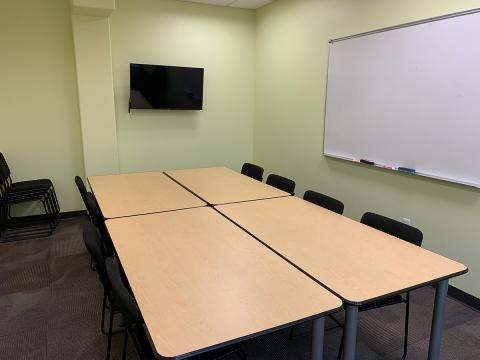 Key Lime Room with lime colored walls, and rectangular tables pushed together to create a central conference table; white board on wall