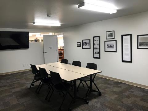 Mayer Meeting room with central conference table, 6 chairs, and a large tv mounted on to wall