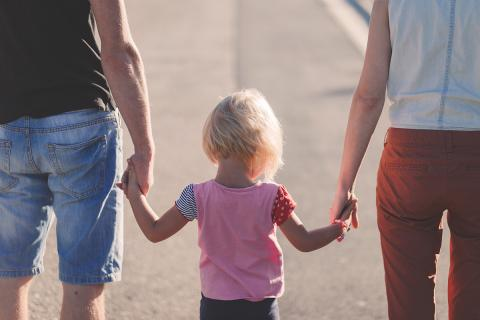 Parents walking hand in hand with child
